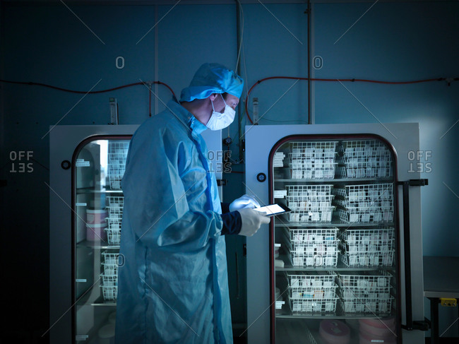 Worker using digital tablet to check archived electronic components in nitrogen atmosphere in clean room laboratory