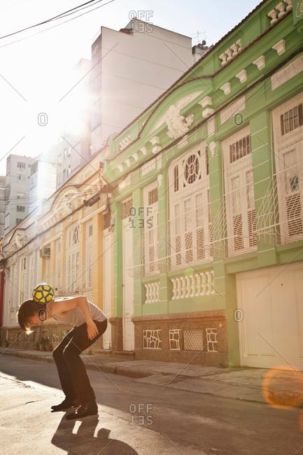 Student celebrating with soccer skills in the street, Rio de Janeiro, Brazil
