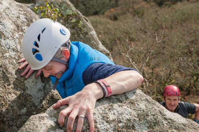 Female rock climber gripping rocks