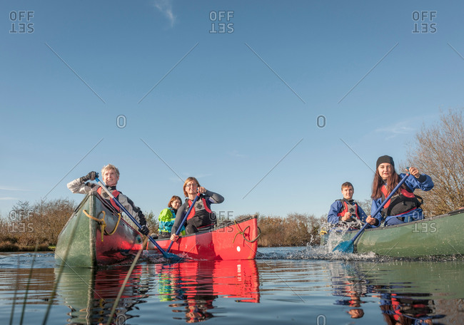Group of people canoeing on river