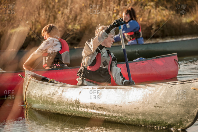 Mid adult woman turning around in canoe