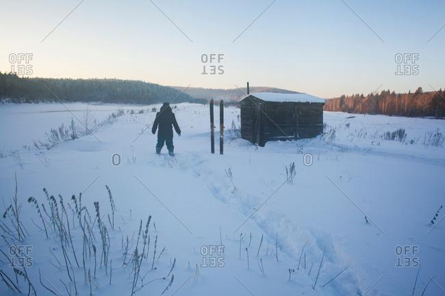 Rear view of man in snow covered landscape, Sarsy village, Sverdlovsk Oblast, Russia