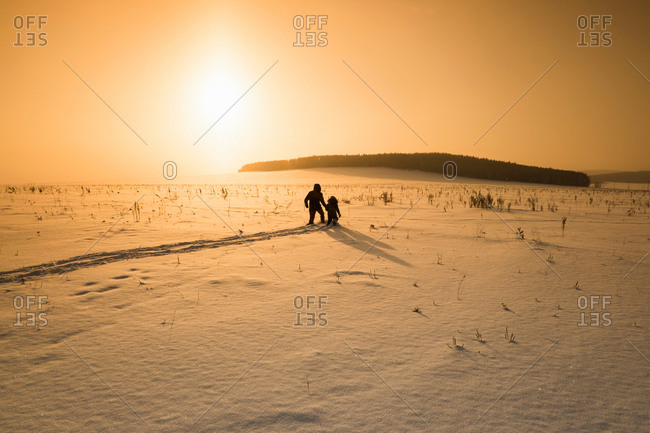 Silhouetted man and son walking in snow covered landscape at sunset, Sarsy village, Sverdlovsk Oblast, Russia