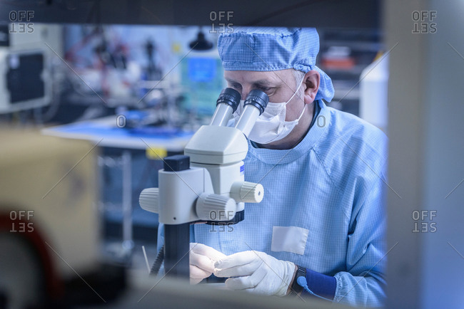 Electronics worker checking component with microscope in clean room