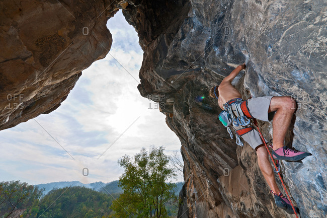 "Male climber climbing the route ""sandbag"" at Crazy Horse Buttress close to Chiang Mai, Thailand"