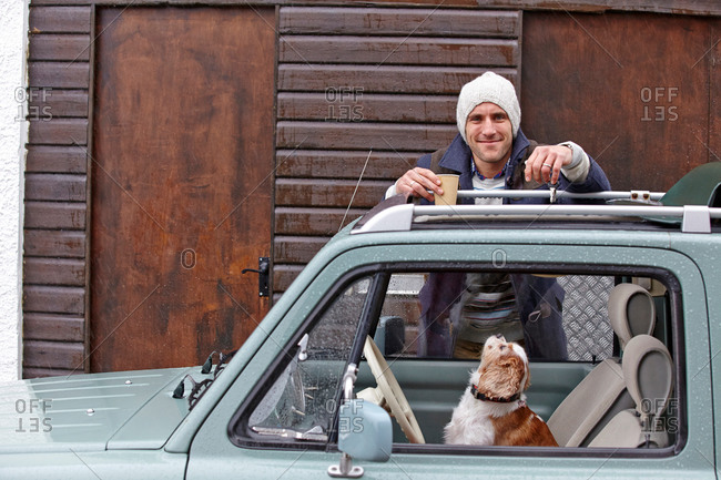 Portrait of mid adult man leaning against van whilst dog looks up