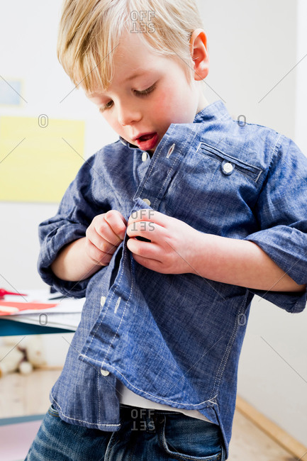 Boy buttoning shirt at home