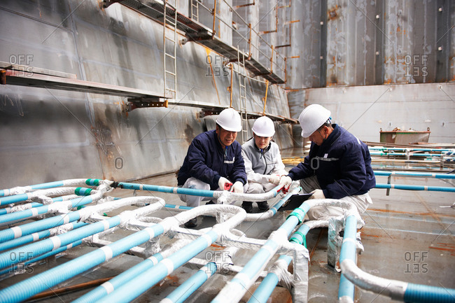 Workers checking pipework on container ship at shipyard, GoSeong-gun, South Korea