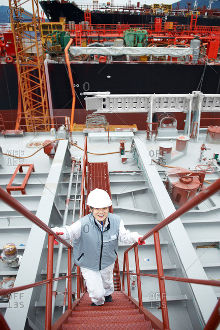 Portrait of worker on steps at shipping port, elevated view, GoSeong-gun, South Korea