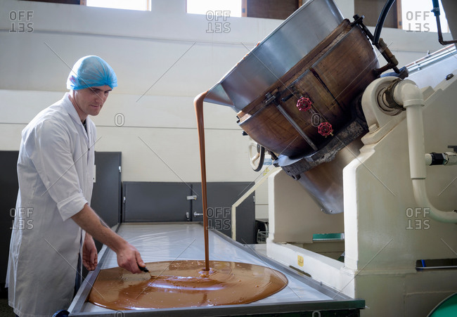 Worker spreading confectionery fudge poured in chocolate factory