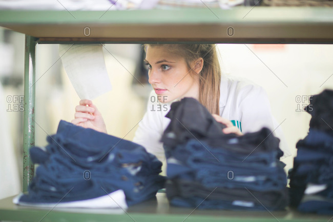 Woman behind shelves of jeans in laundry