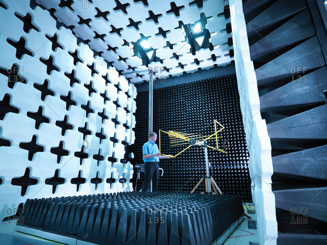 Engineer checking the bilog antenna set up for electromagnetic compatibility (EMC) radiated emissions in anechoic chamber with energy absorbers