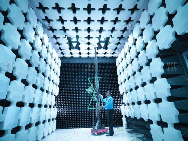 Engineer checking a bilog antenna's height for electromagnetic compatibility (EMC) radiated immunity testing in a semi anechoic chamber