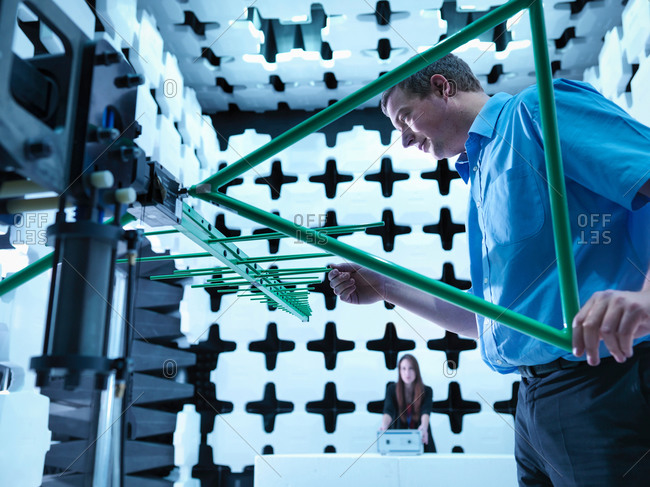 Engineers checking a bilog antenna for electromagnetic compatibility (EMC) radiated immunity testing in a semi anechoic chamber relative to the electronic equipment under test (EUT)