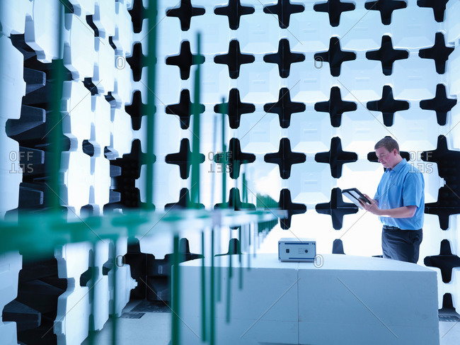 Engineer checking the equipment under test (EUT), in a semi anechoic chamber with energy absorbers and bilog antenna set up for electromagnetic compatibility (EMC) radiated immunity testing