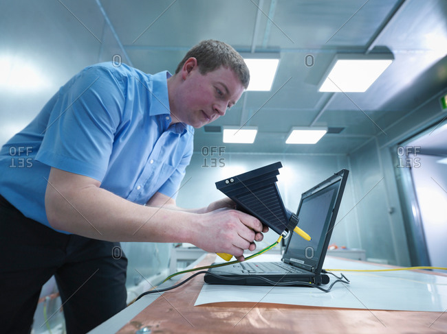 Engineer carrying out electro static discharge (ESD) testing using air discharge probe on copper table in screened room