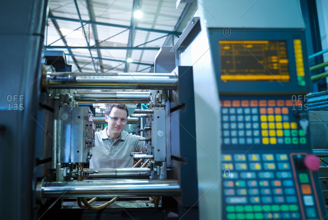 Worker with plastic injection moulding machine in plastics factory