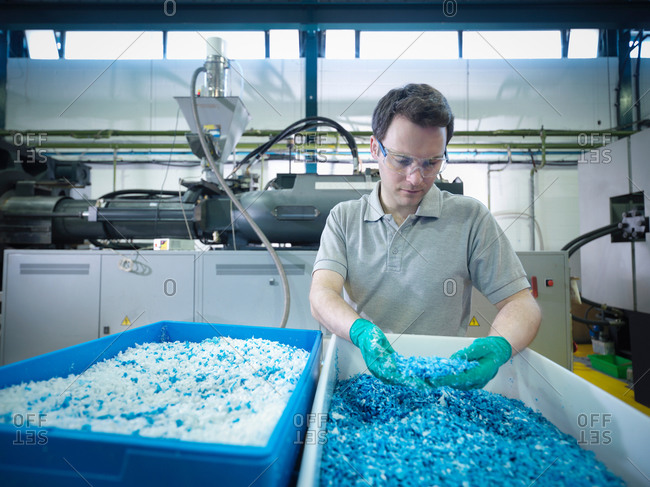 Worker inspecting recycled plastic in plastics factory