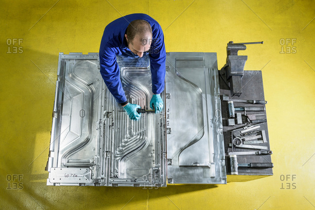Overhead view of worker finishing metal mould in plastics factory