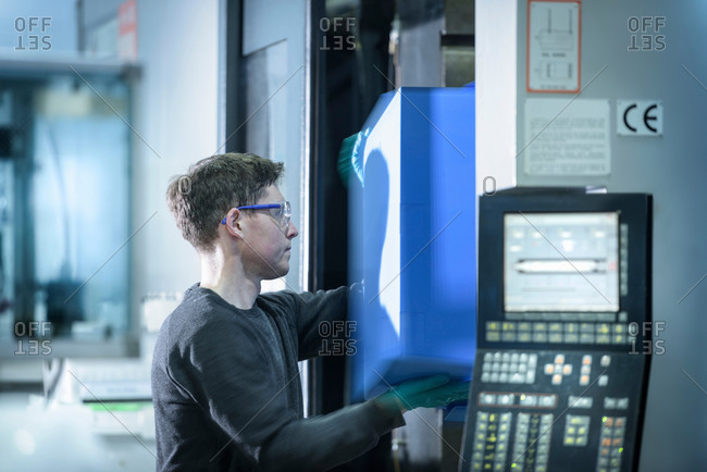 Worker removing plastic part from injection moulding machine in plastics factory