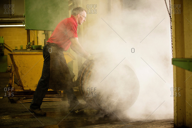 Male cooper rolling whisky cask in cooperage