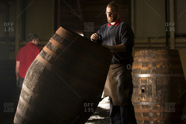 Male cooper working in cooperage with whisky cask