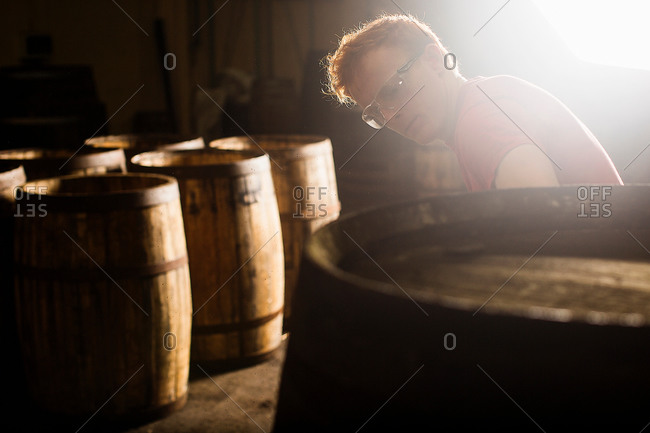Young man working in cooperage with whisky casks
