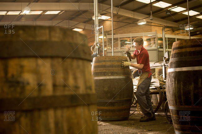 Young man making whisky cask in cooperage