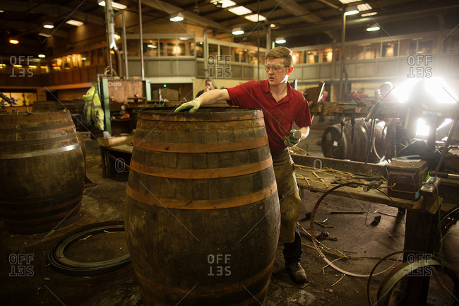 Mid adult man making whisky cask at cooperage
