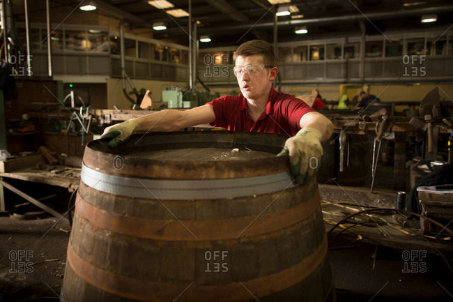Young man making whisky cask at cooperage