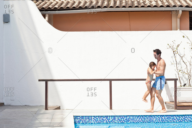 Father and daughter by side of outdoor pool, father lifting daughter