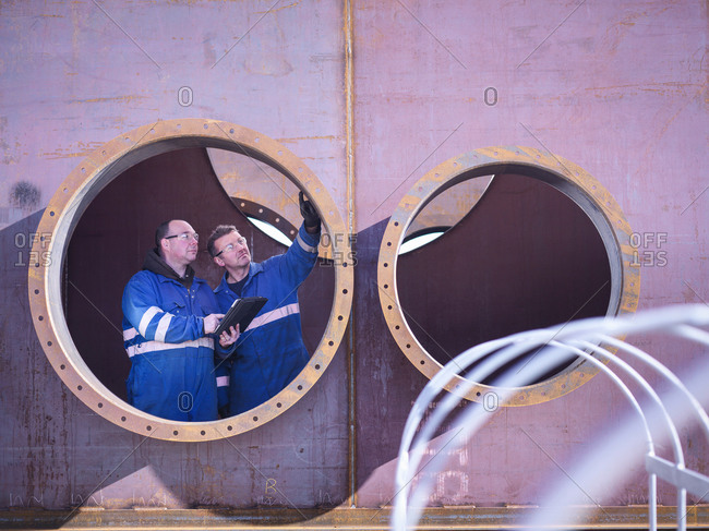 Engineers inspecting large steel superstructure in engineering factory