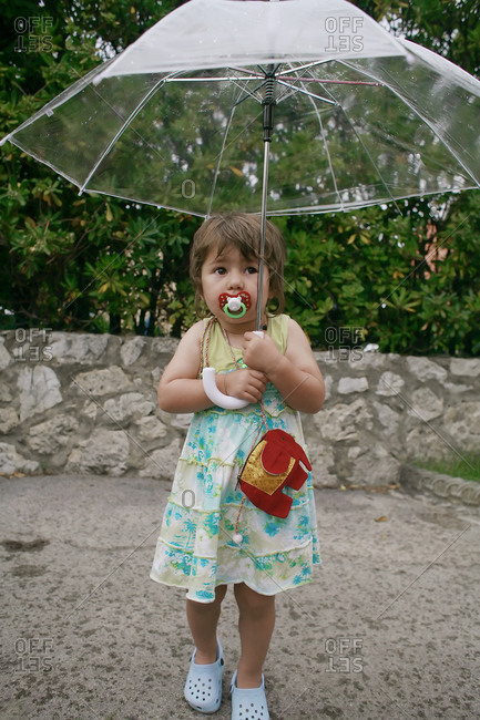 Girl with a pacifier standing outdoors in a sundress holding an umbrella