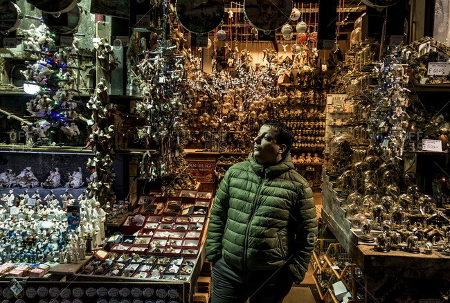 Naples, Italy - March 28, 2016: Man standing near a storefront display in the Decumani area of Naples, Italy