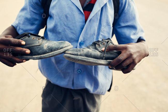 Namibian child holding shoes
