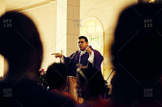 Rincon, Cuba - December 16, 2015: A priest preaching to congregation