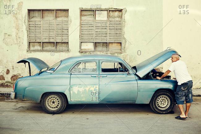 Havana, Cuba - December 21, 2015: Man fixing car in Cuba
