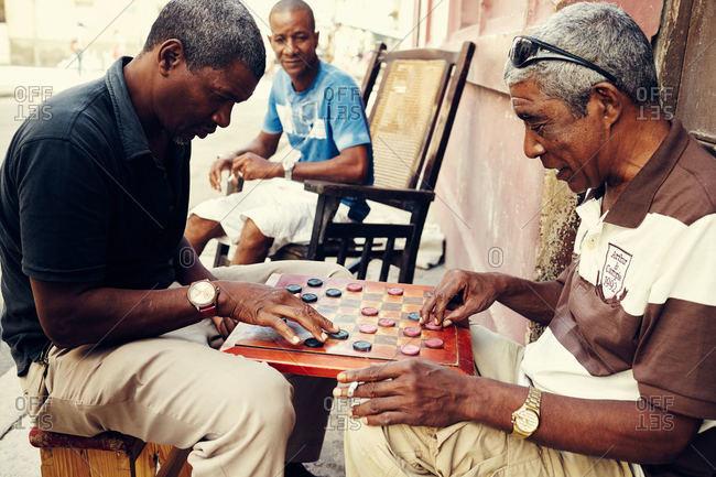 Havana, Cuba - December 13, 2015: Cuban men playing checkers