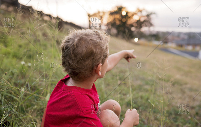 Boy sitting on a hillside pointing to something in the distance