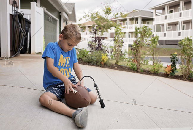 Little boy inflating a football