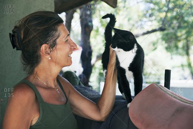 Mature woman stroking cat
