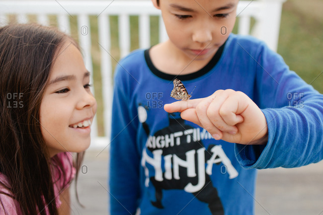 Sister looking at butterfly on brother's finger