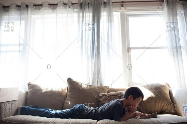 Boy lying on sofa reading a book