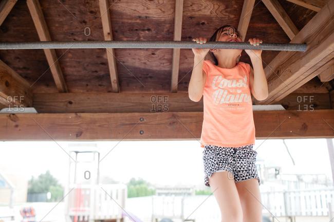 Girl doing chin-up on bar below deck