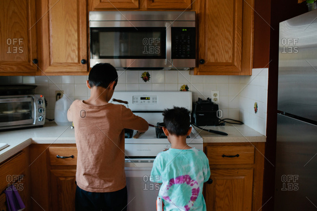 Two young boys cooking at stove together