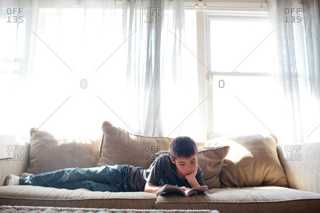 Young boy lying on sofa reading a book