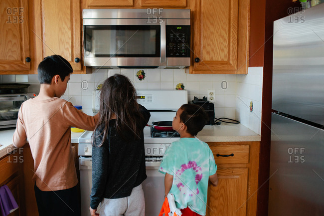 Siblings cook together at kitchen stove