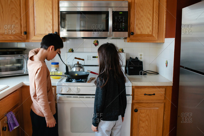 Boy and girl cooking together at stove