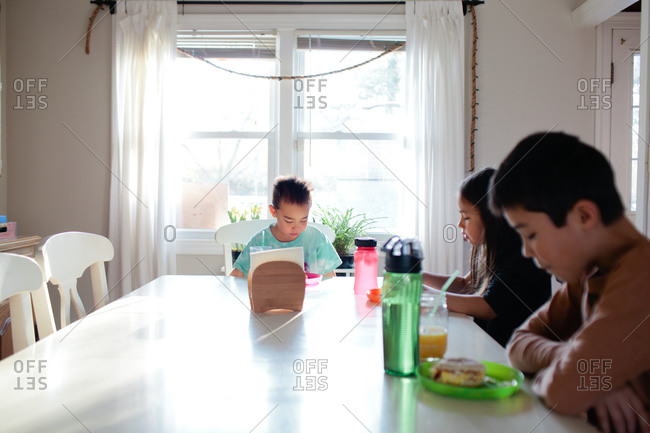 Three young siblings having meal together at dining table