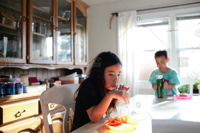 Young girl drinking from straw at dining table with brother